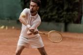 Fotografie pěkný retro stylu tenisový hráč udeří míč na tenisový kurt