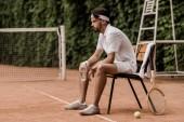 a jóképű retro stílusú tenisz játékos ül a széken, üveg víz teniszpálya oldalnézete