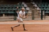 koncentrované retro stylu muž hrát tenis na kurtu