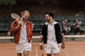 Photo smiling retro styled tennis players walking with rackets at tennis court