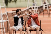 Fotografie smiling retro styled tennis players giving high five at tennis court