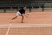 Fotografie retro stylu pohledný muž s tenisem raketou tenisový kurt