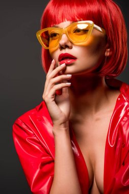close-up portrait of beautiful young woman in red latex jacket on bare skin and vintage yellow sunglasses isolated on grey