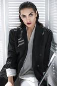 Fotografie Elegantní módní dívka s make-upem pózuje v černé sako