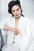 Fotografie brunetka elegantní dívka pózuje v bílém obleku a elegantní klobouk