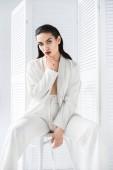 Fotografie atraktivní polovinu nahý model představuje v bílé módní oblek