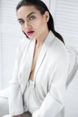 Krásná sexy žena pózuje v bílé módní oblek na židli