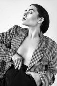 seductive half naked woman posing in retro jacket, isolated on grey, black and white