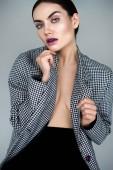 elegant seductive half naked woman posing in vintage jacket, isolated on grey