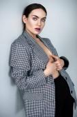 Fotografie elegantní atraktivní půl nahá mladá žena pózuje v vintage sako, Grey