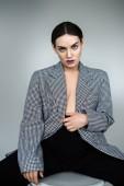 Fotografie krásná půl nahá žena pózuje v elegantní vintage sako, izolované Grey