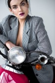 Photo fashionable woman in jacket and net veil posing on vintage scooter, isolated on grey