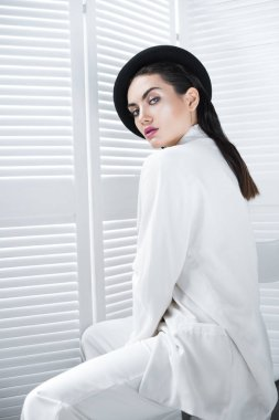 seductive young woman posing in beret and white fashionable jacket