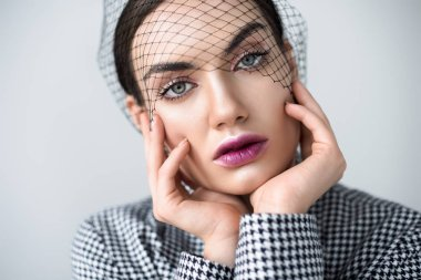 beautiful girl with makeup posing in jacket and vintage net veil, isolated on grey