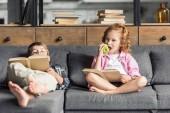Fotografie niedliche kleine Bruder und Schwester lesen Bücher auf couch zu Hause