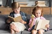 Fotografie kleinen Bruder und Schwester, die Bücher lesen auf dem Sofa zu Hause konzentriert