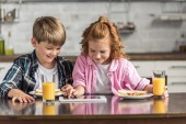 Fotografie Glückliche kleine Bruder und Schwester mit Tablet während des Frühstücks in Küche