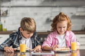 Fotografie kleinen Bruder und Schwester mit tablet während des Frühstücks in Küche