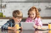 Fotografie kleinen Bruder und Schwester mit Tablet während des Frühstücks überrascht