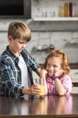 Fotografie entzückende kleine Bruder seine lächelnde Schwester Glas Orangensaft verleiht