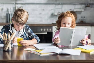focused little siblings doing homework together at kitchen
