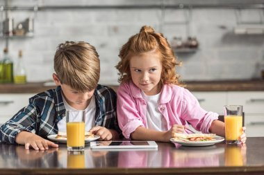 cute little brother and sister using tablet during breakfast at kitchen