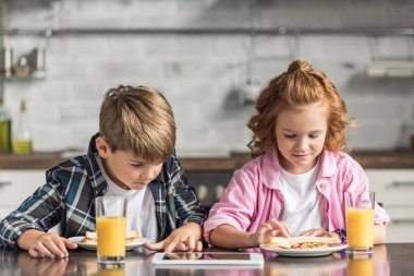 little brother and sister using tablet during breakfast at kitchen