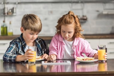 adorable little brother and sister using tablet during breakfast