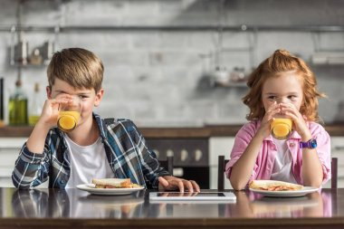 little brother and sister drinking orange juice together during breakfast