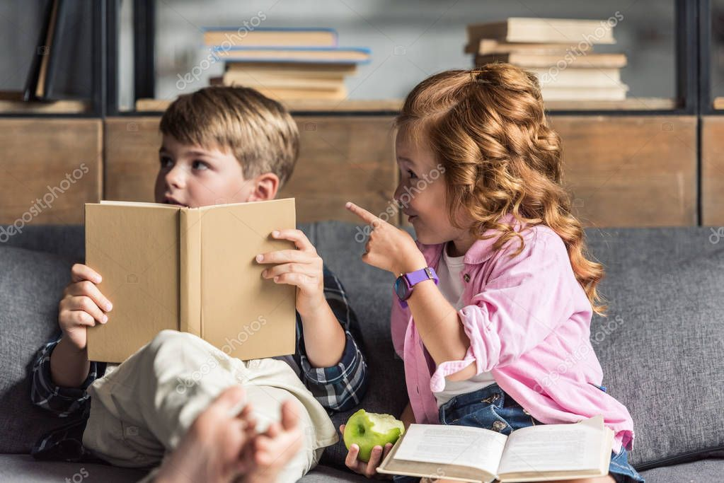 Cute little schoolboy reading book on couch while his sister pointing somewhere stock vector