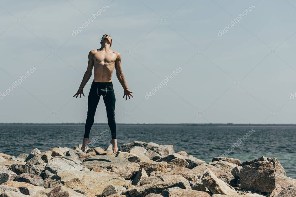 handsome shirtless contemporary dancer jumping on rocky coast