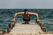 Fotografie atletický muž dělá push up na dřevěném molu