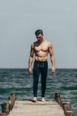 hezký sportovní muž stojí na dřevěném molu