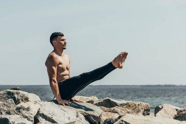 athletic shirtless man doing arm balance on rocky seashore