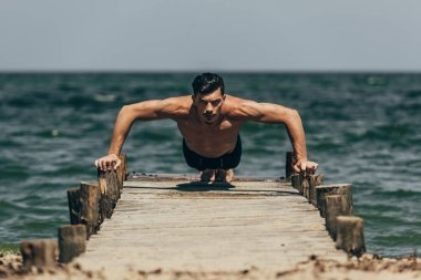 handsome athletic man doing push ups on wooden pier