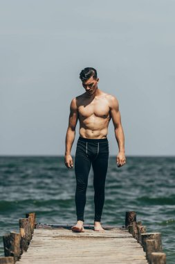 handsome sporty man standing on wooden pier