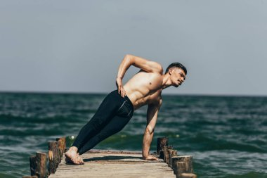 athletic shirtless man doing side plank on wooden pier
