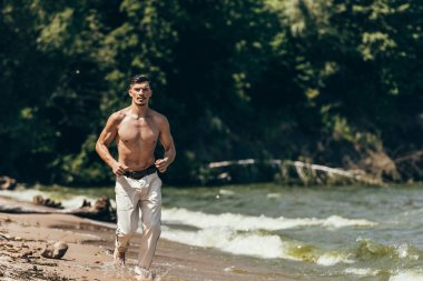 attractive shirtless man jogging on sandy beach