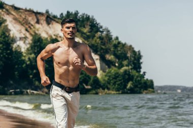 handsome shirtless man jogging on sandy beach