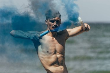 handsome shirtless man with blue and white smoke sticks in front of ocean