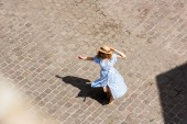Fotografie high angle view of redhead woman in straw hat dancing at city street