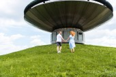 rear view of redhead couple holding hands and walking on grassy hill in front of modern building