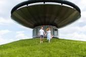 Fotografie redhead couple holding hands and walking on grassy hill in front of modern building
