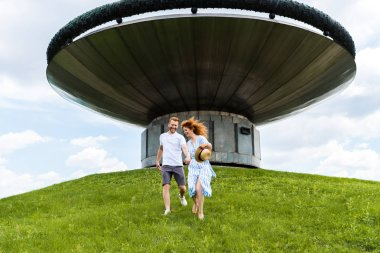 Happy redhead couple holding hands and running on grassy hill in front of modern building stock vector