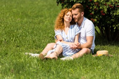redhead man embracing girlfriend and sitting on grass in park