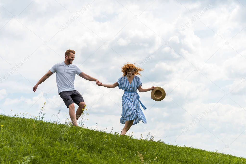 happy redhead couple having fun and running on grassy hil
