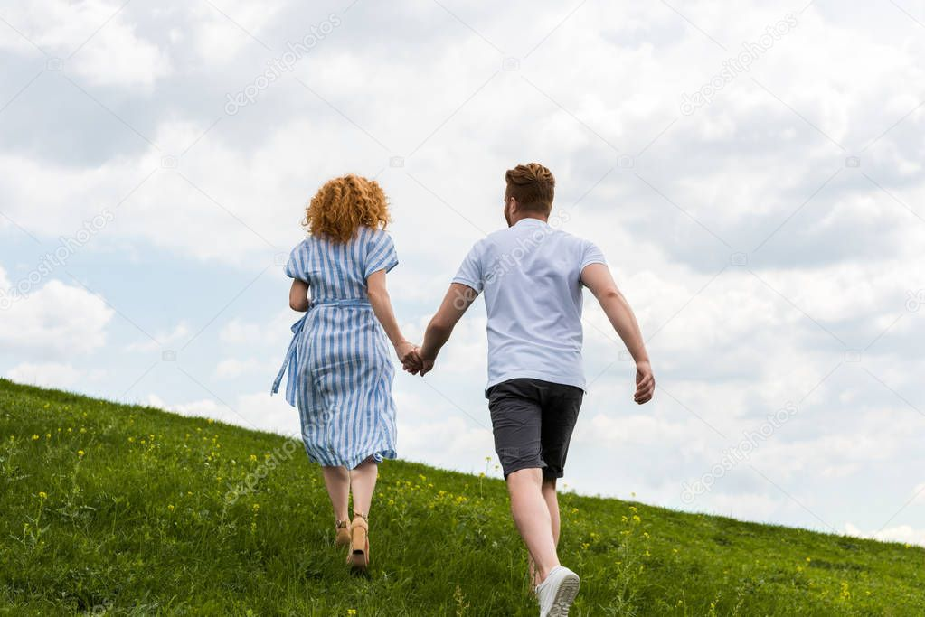 rear view of redhead couple holding hands and running on grassy hill