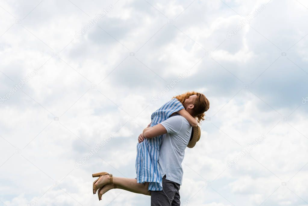 redhead man embracing and holding girlfriend against cloudy sky