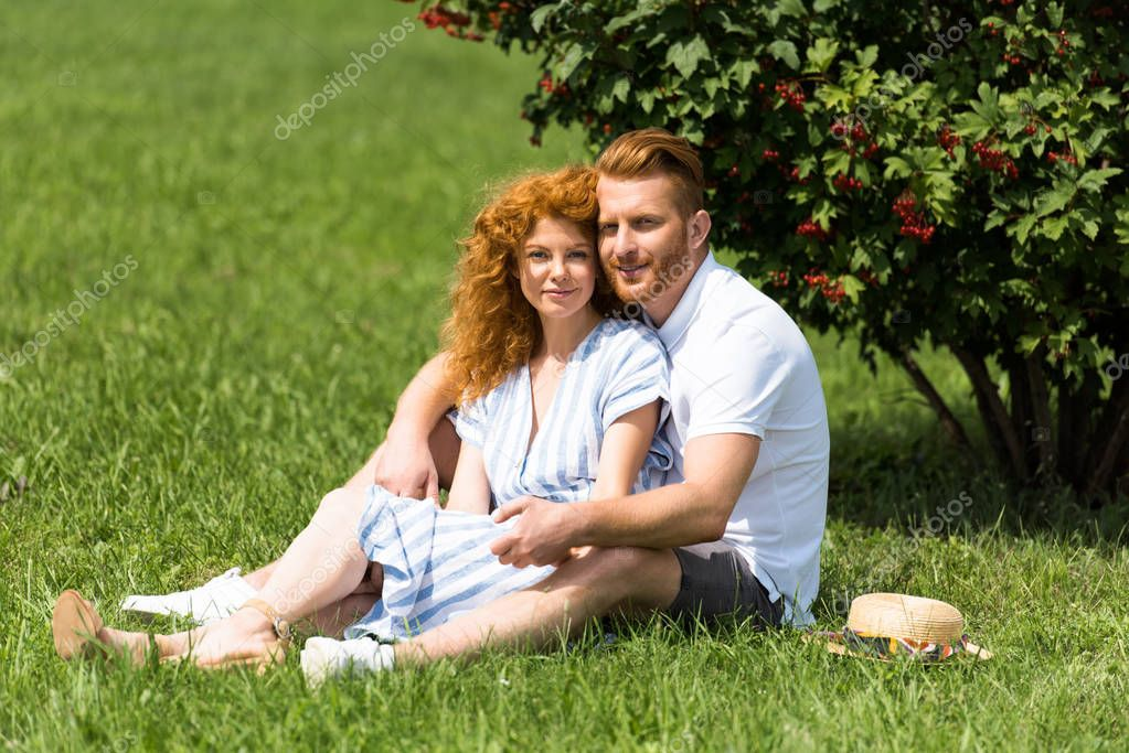 redhead couple looking at camera and sitting on grass in park