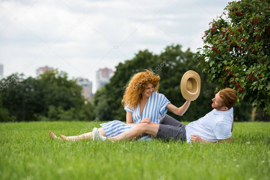 smiling redhead woman trying to putting on own straw hat on boyfriend head on grass in park